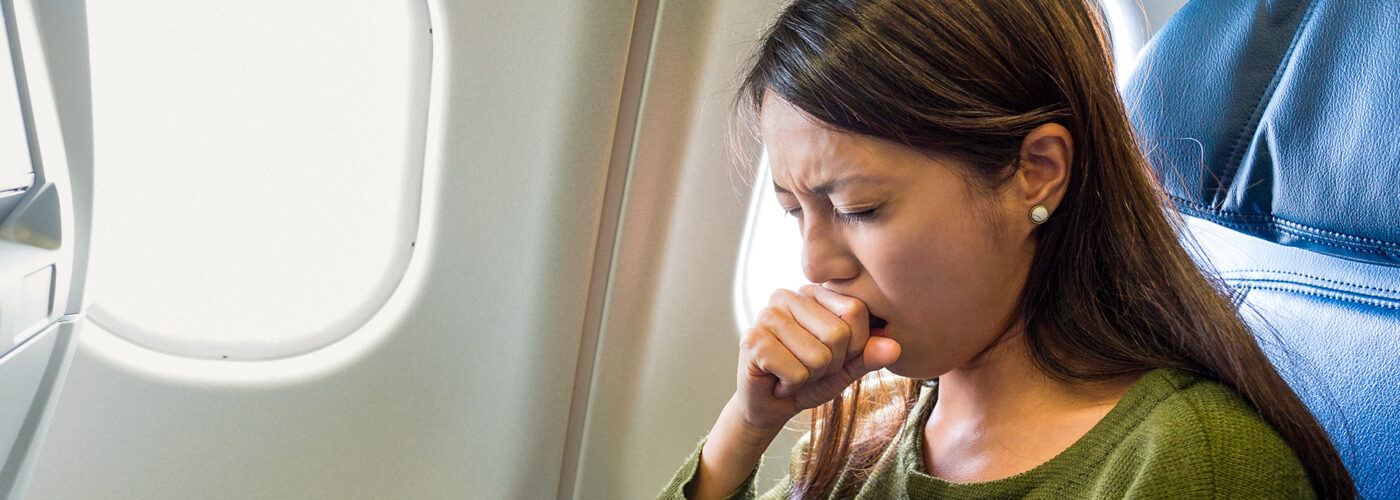 Woman feeling sick inside air plane coughing