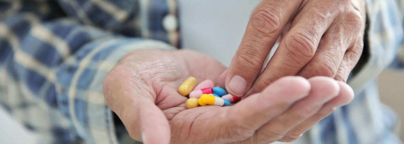 man holding medications.
