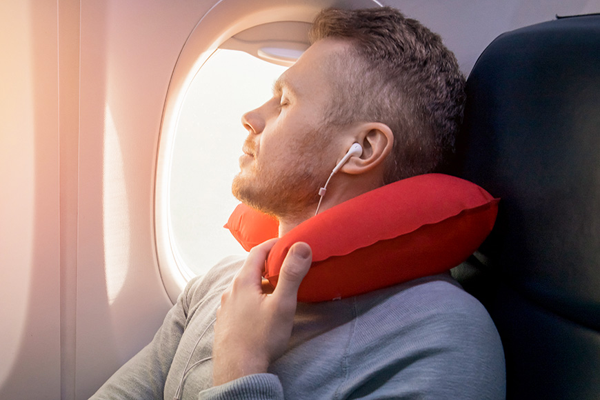 Male passenger of airplane listens to music and enjoys pillow for sleeping in chair