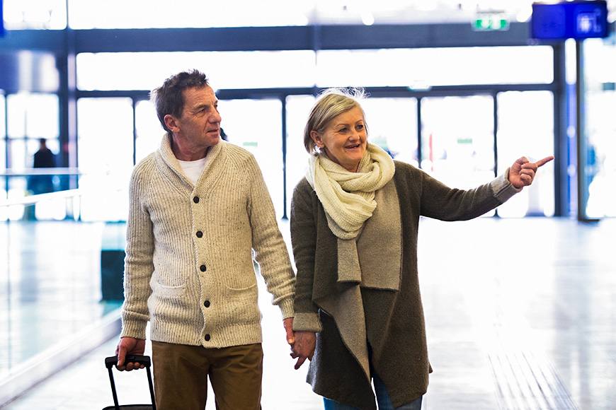 senior couple walking through airport pointing wearing scarf and sweaters