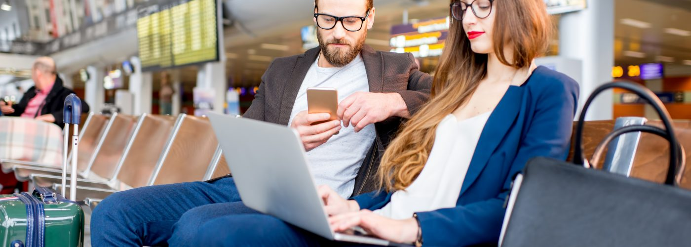 Couple using Wi-Fi at airport
