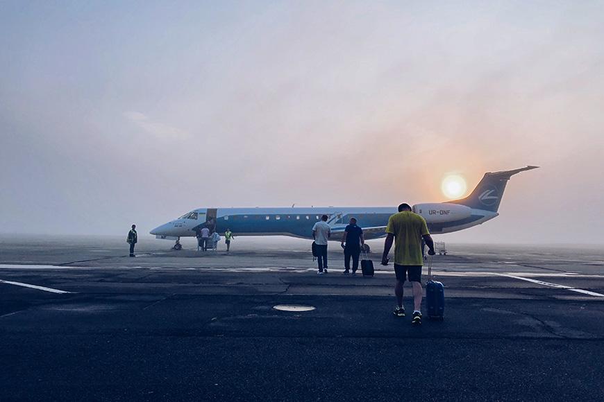 sunrise man boarding plane rolling luggage