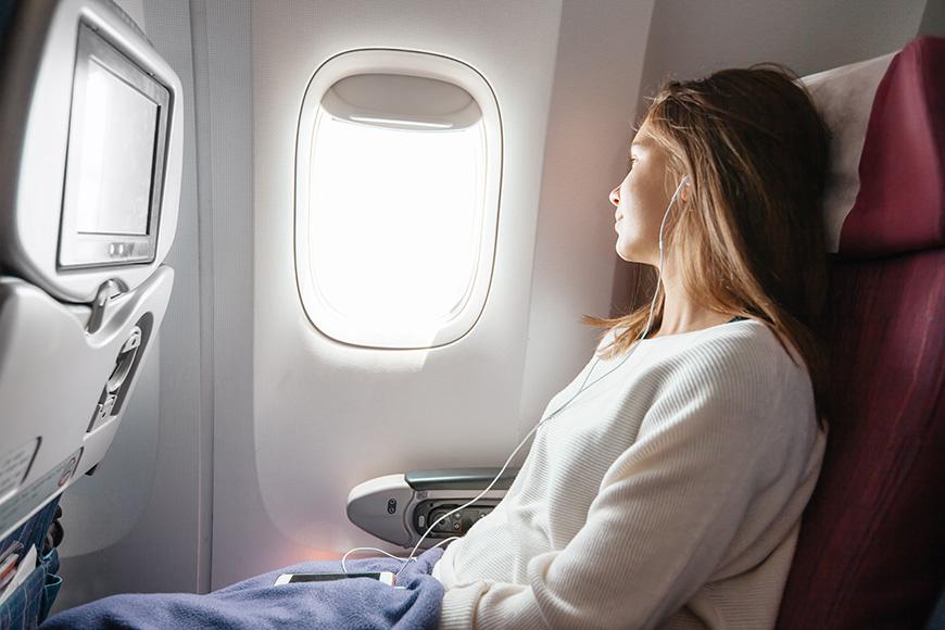 Teenage girl looking at plane window during flight.