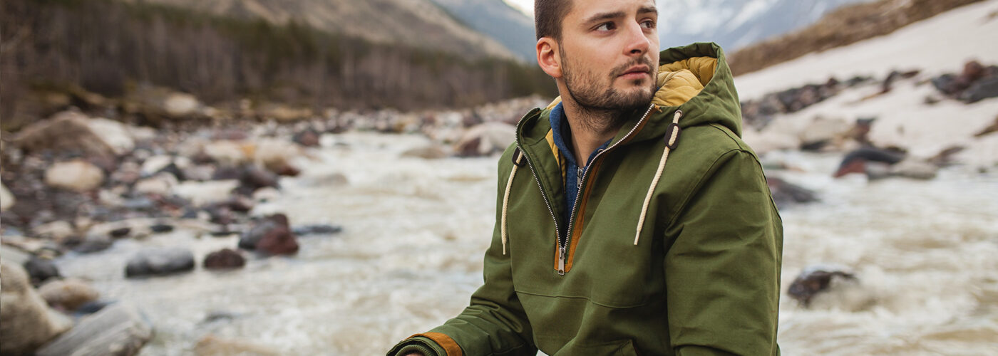 sitting by the river, wild nature, winter vacation, hiking, traveling, backpacker, warm clothes, anorak