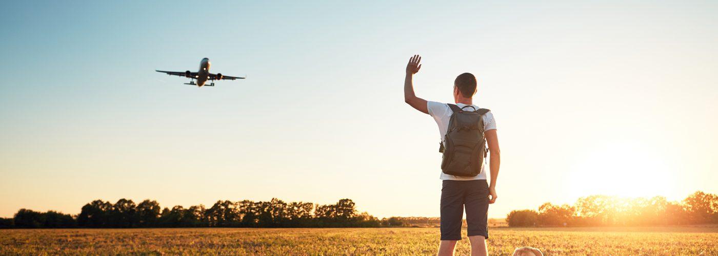 man waving at airplane overhead.