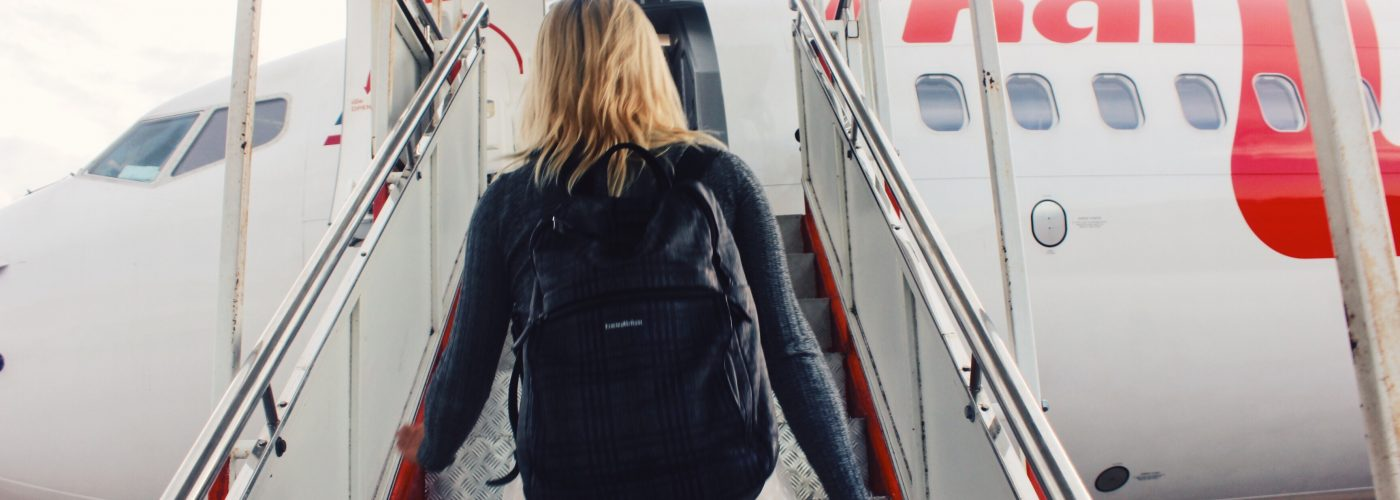 woman boarding plane wearing backpack
