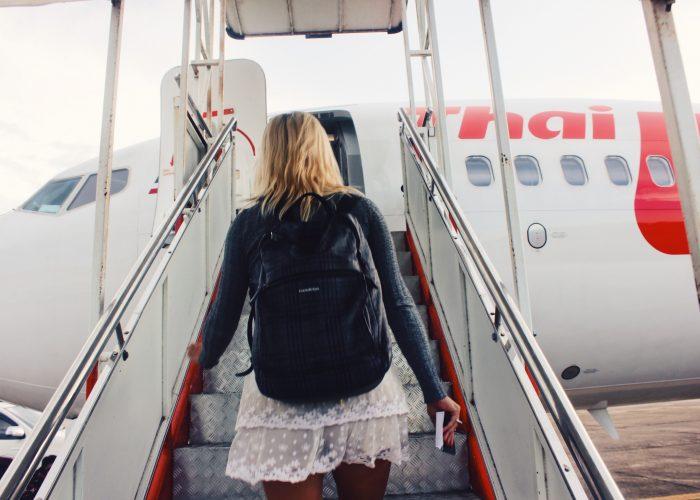 woman boarding plane wearing backpack