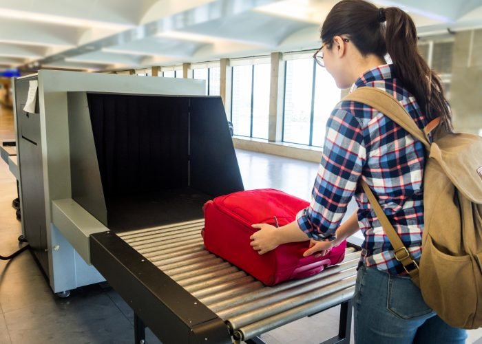 woman putting bag on security xray tsa screening