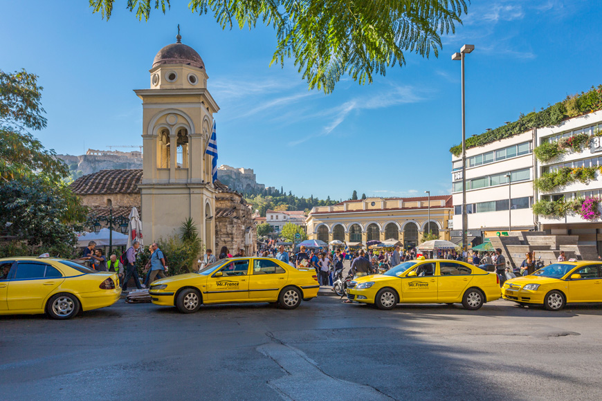 View of Greek Orthodox Church in Monastiraki Square and line of yellow cabs