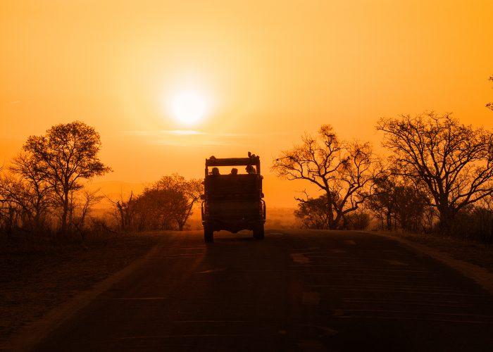 Silhouette of safari vehicle against sunset