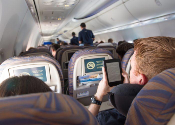 man reading kindle on plane.