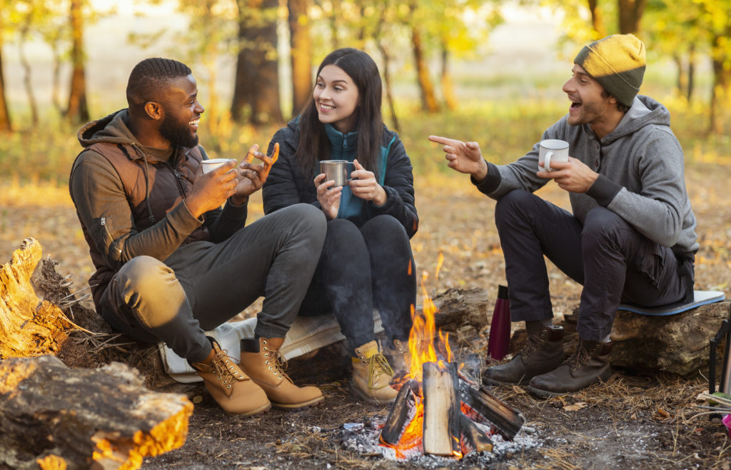 Three friends laughing around a campfire