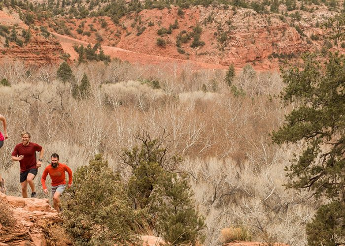 male and female running up canyon in activewear.