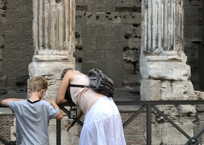 Tour guide points to ancient street level in Rome