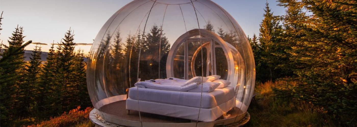 A bed inside an insulated bubble overlooking forest scenery in Iceland
