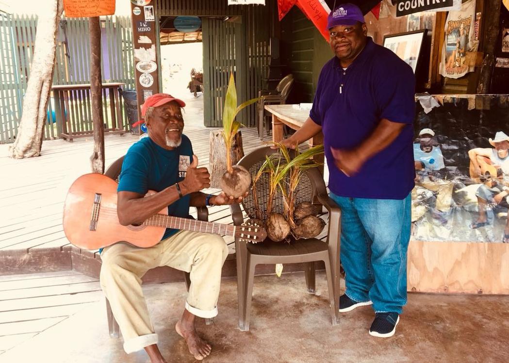 Men holding coconut palm seedlings