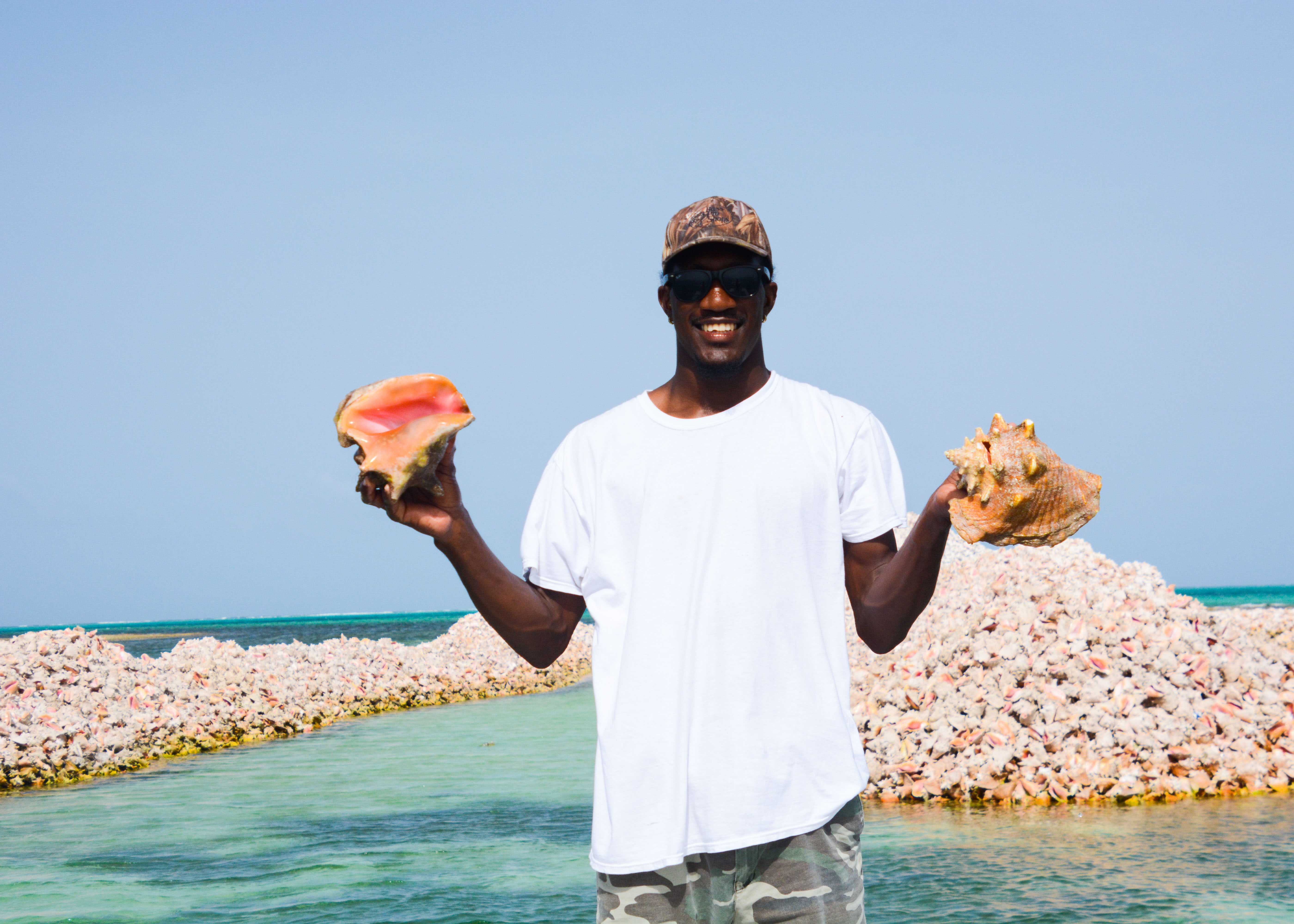 Man holding conch shells on anegada in the bvi