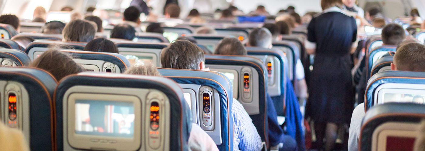 flight attendant moving through airplane cabin
