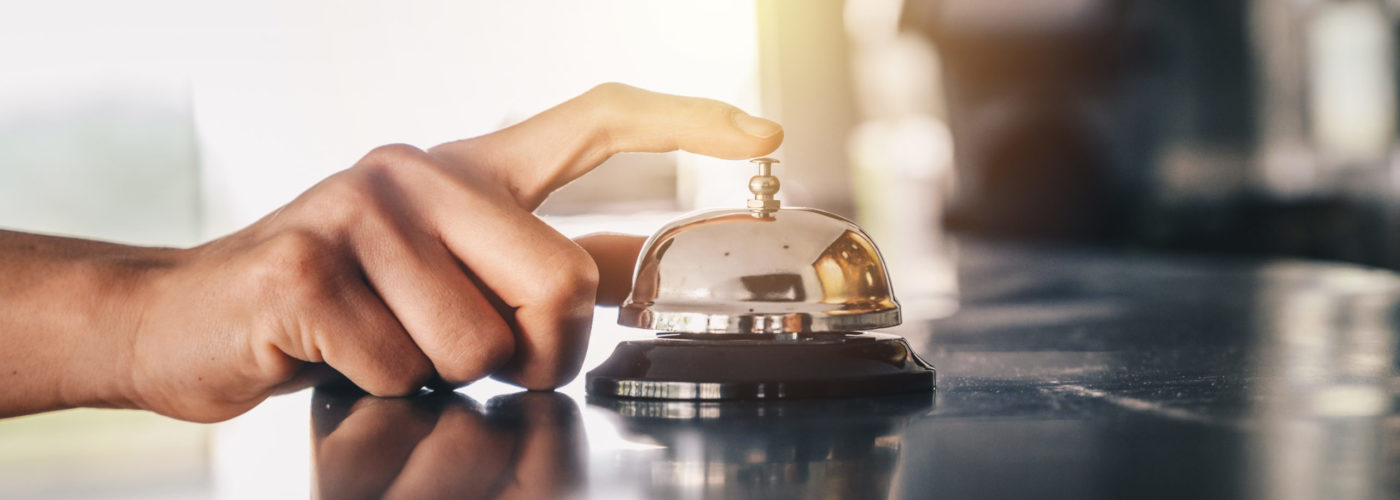 Hand ringing front desk hotel bell