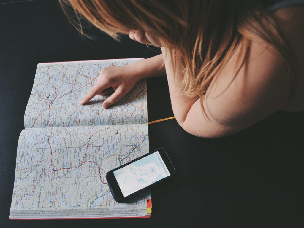 woman reading a map with phone out