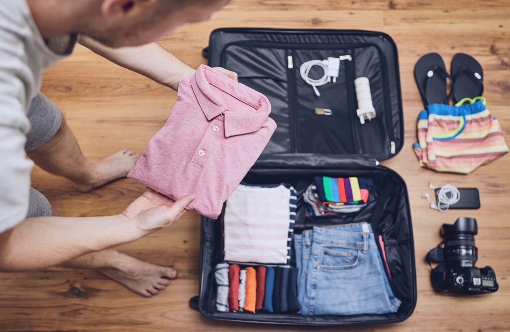 man packing suitcase for upcoming trip with gear spread out