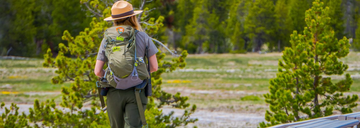 female national park ranger walking in park