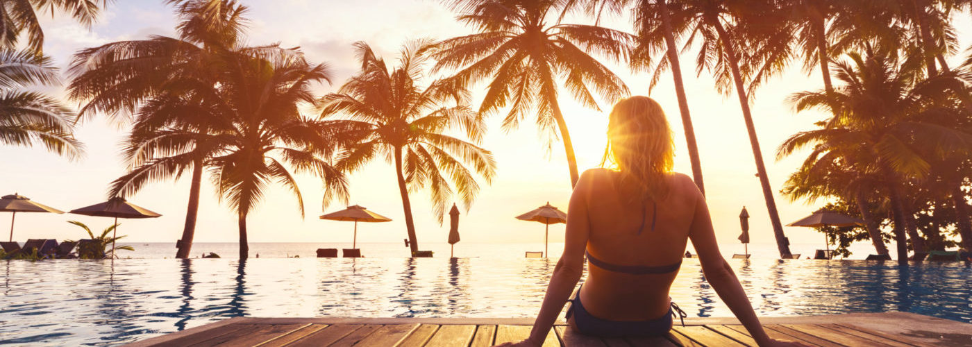 Woman relaxing on a pier in front of a pool and palm trees