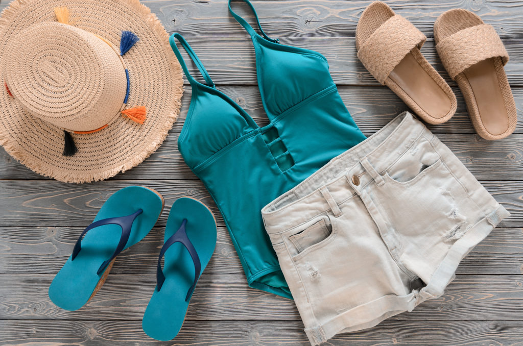 Beach clothing laid out on wooden backdrop