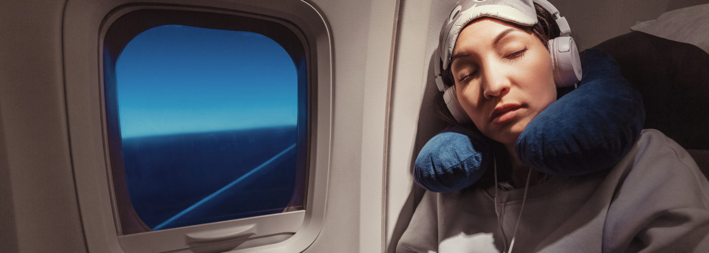 Woman sleeping on plane with neck rest, eye mask, and headphones