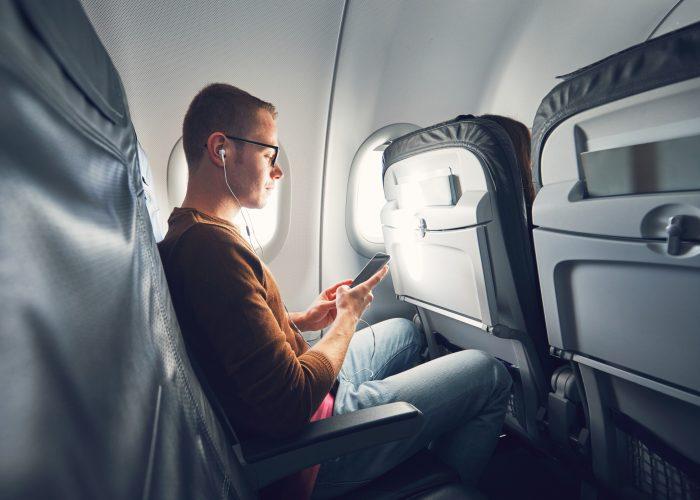 Man on airplane wearing headphones - hero