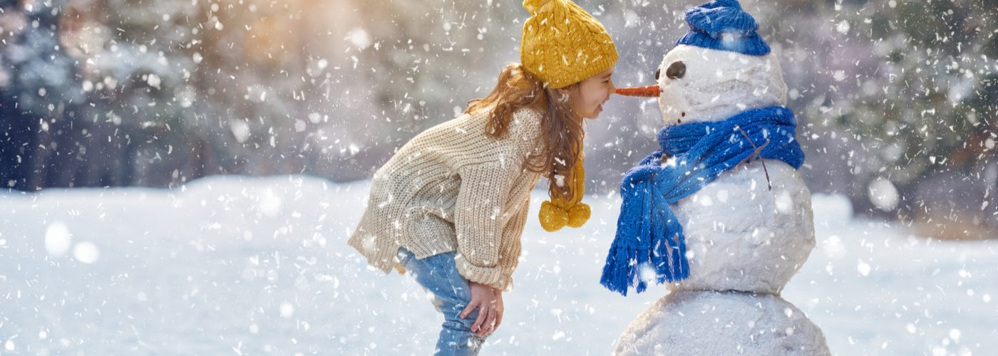 girl playing with snowman on a snowy winter walk