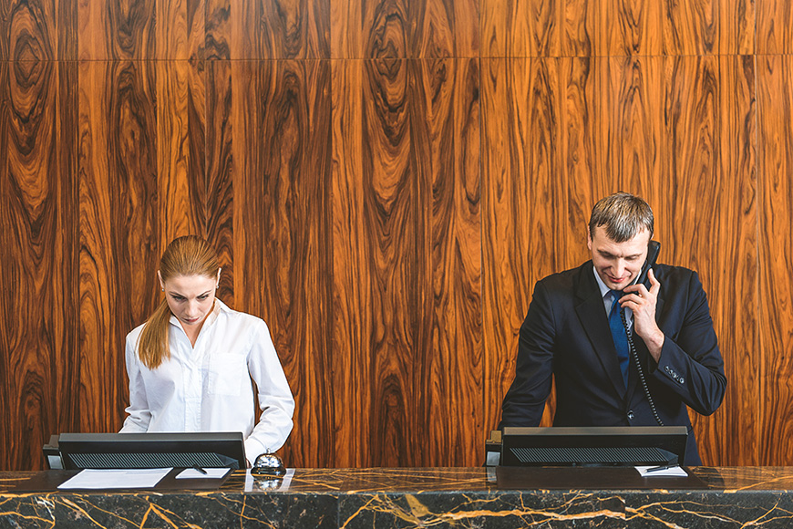 two hotel employees standing at reception desk