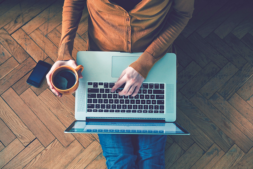 man typing on laptop with a coffee in hand
