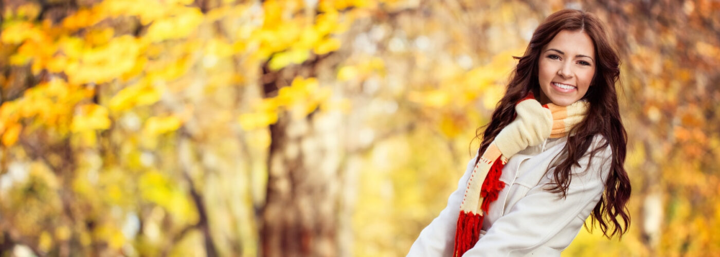 smiling woman in white coat in fall.