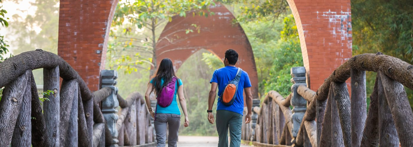 two people walking along bridge touring with small backpacks on