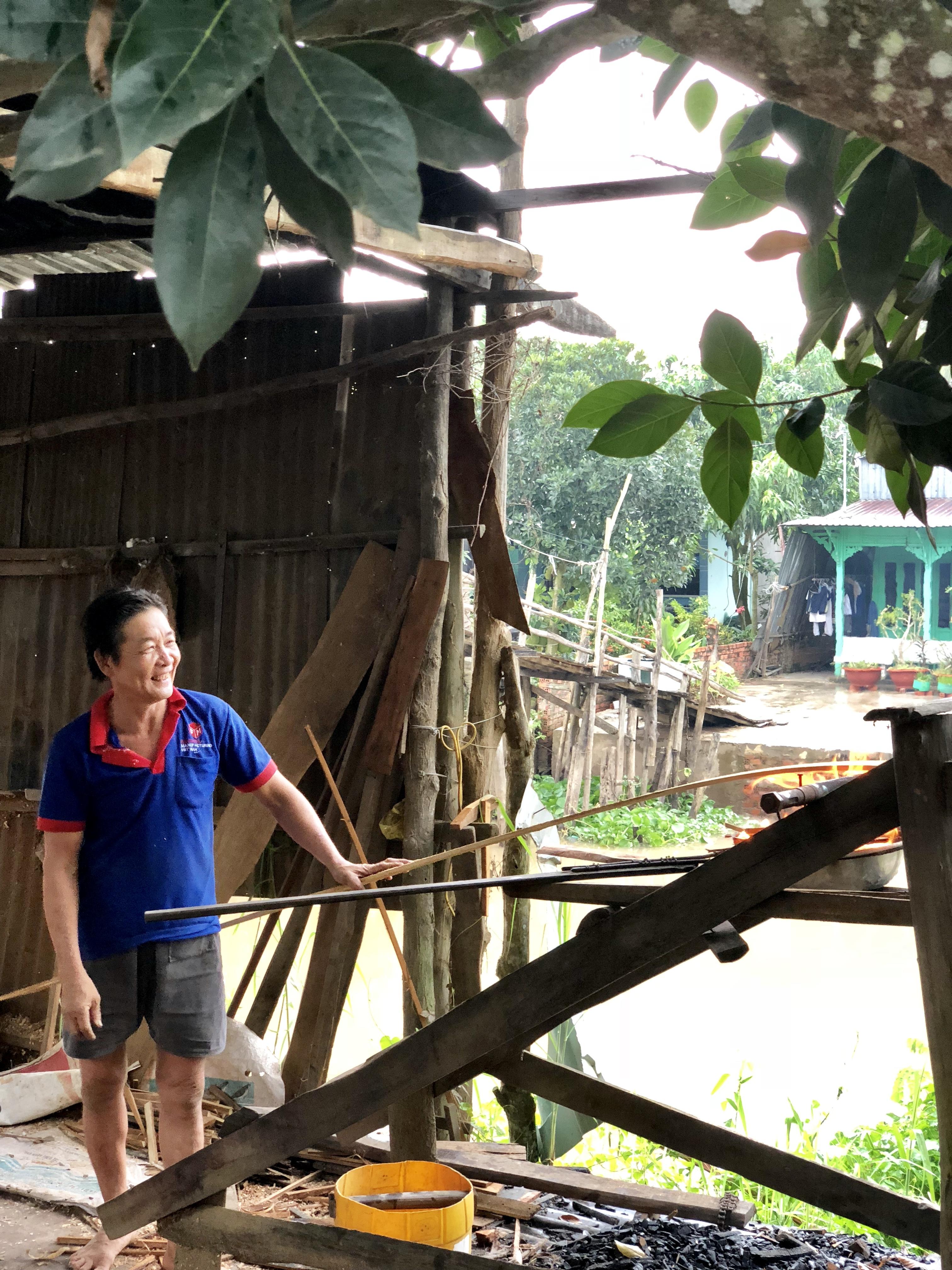 Sampan maker heats wood over a fire in vietnam