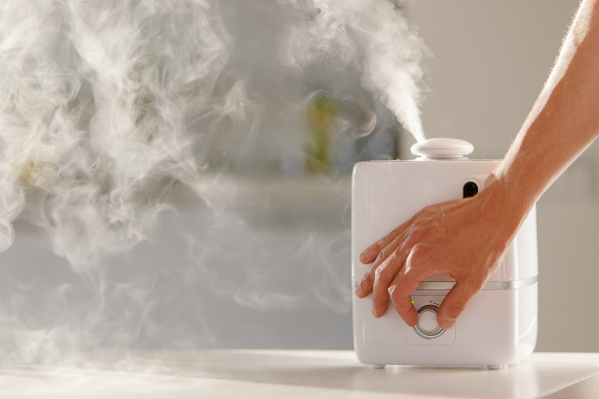 Hand turn on aroma oil diffuser the table at home