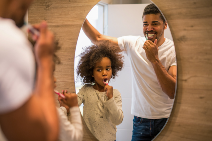 African american girl brushing teeth with dad