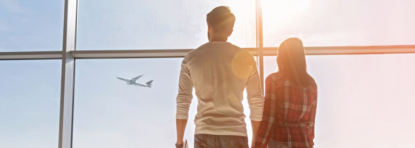 traveling couple at airport staring at airplane.