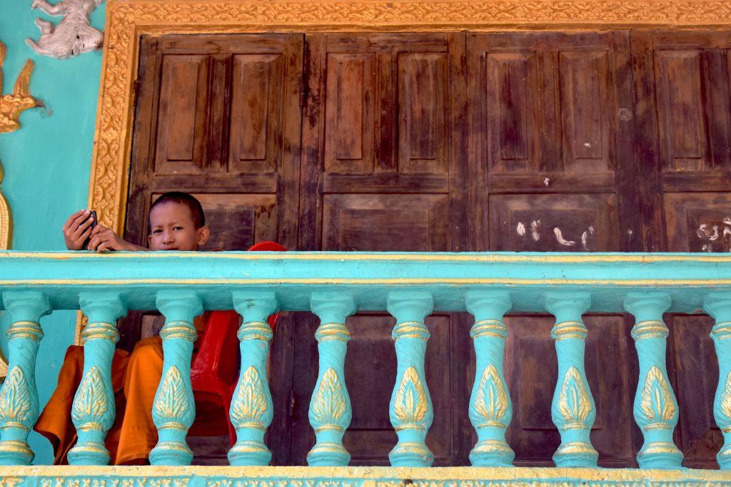 a young monk looks out over the temple