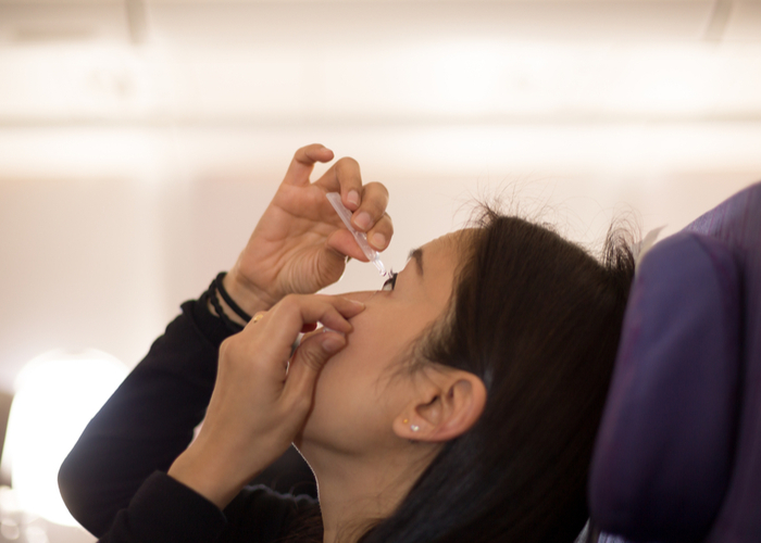 person using eye drops on airplane