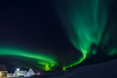 northern lights in a dark sky over houses