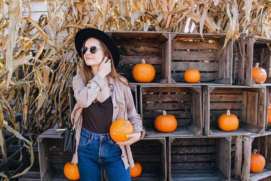 woman holding pumpkin at farm