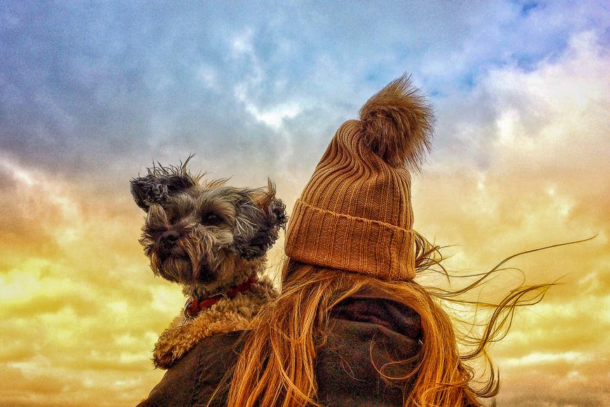 woman wearing hat holding pet dog