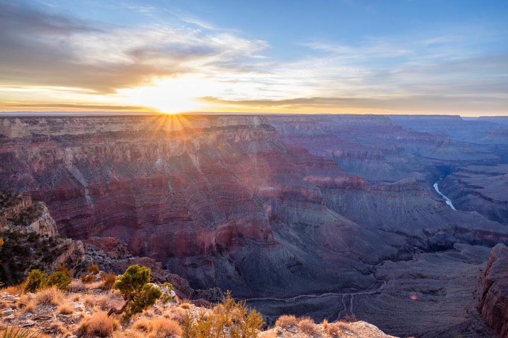 Sun peeking above the rim of grand canyon