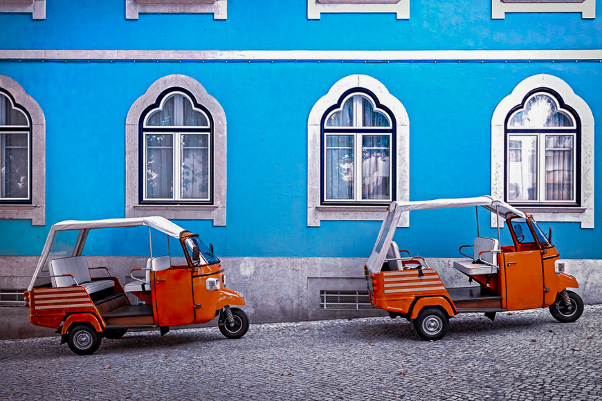 Tuk tuk vehicle in front of blue facade building in the Lisbon, Portugal.