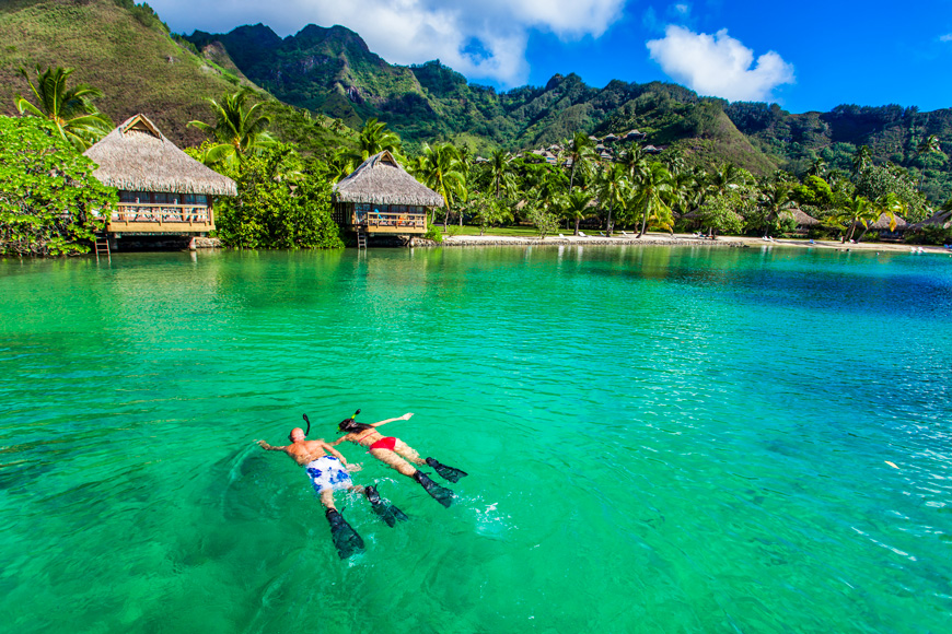 Young couple snorkeling over reef next to resort on a tropical island with over-water villas