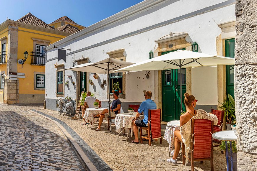 People are sitting at the outside terrace of a small cafe in the historic centre of Faro