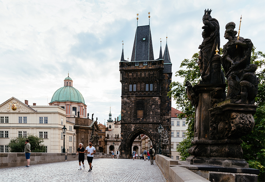 Charles bridge at sunrise with people prague summer in europe