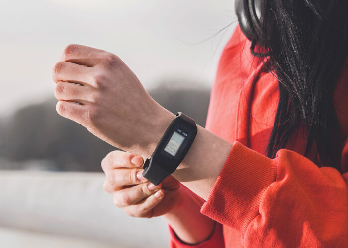 Closeup cropped photo of female runner putting a pedometer on her wrist